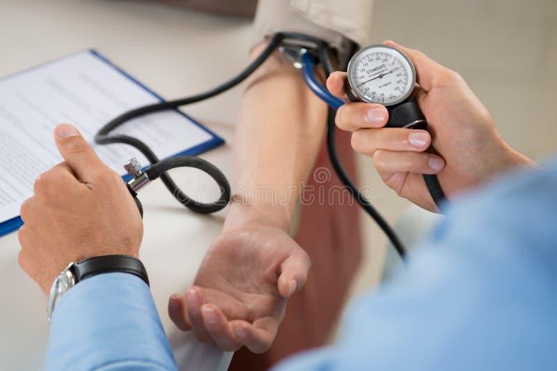 El doctor Measures Pressure In el paciente imágenes de archivo libres de regalías