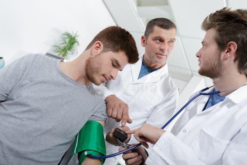 El doctor mide al hombre joven paciente de la presión arterial fotografía de archivo libre de regalías