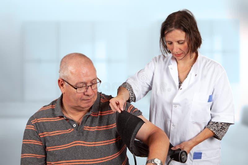 El doctor mide la presión arterial foto de archivo libre de regalías