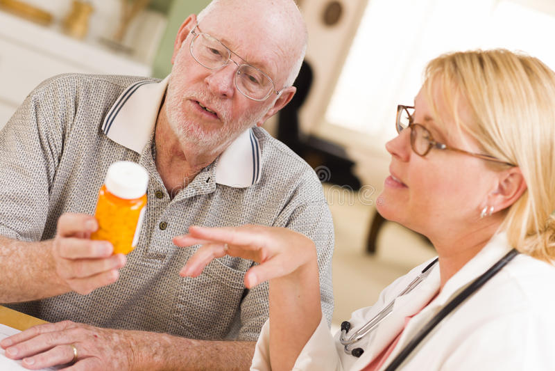 El doctor o enfermera Explaining Prescription Medicine al hombre mayor foto de archivo