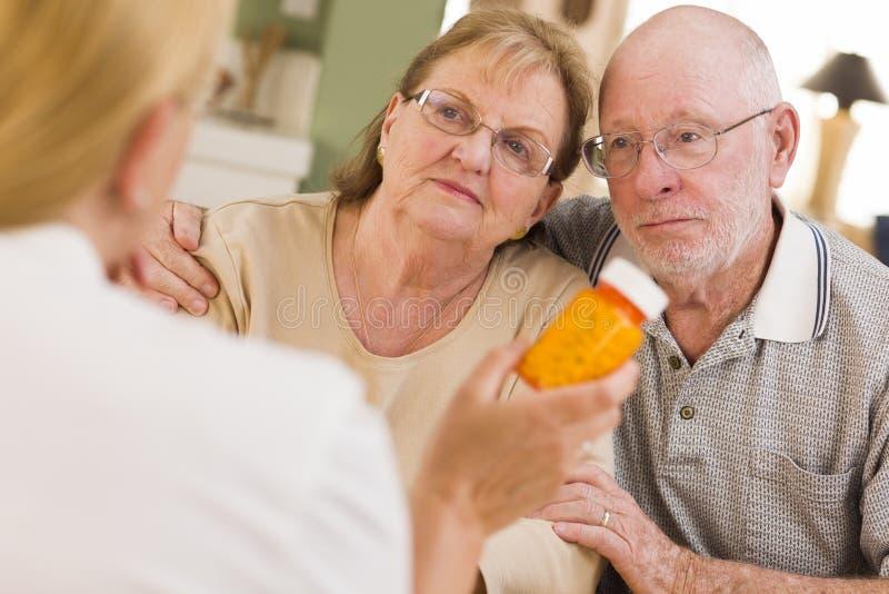 El doctor o enfermera Explaining Prescription Medicine a Coupl mayor fotografía de archivo libre de regalías