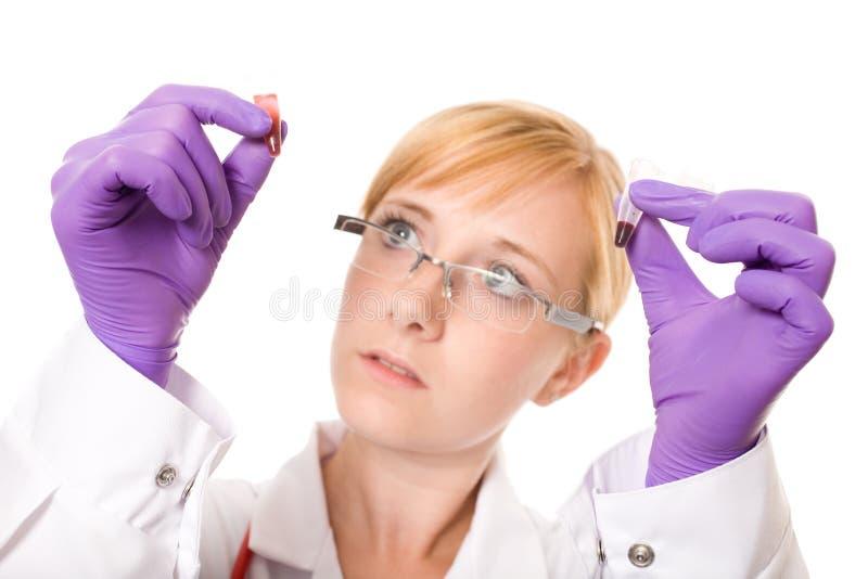 El doctor o la enfermera de sexo femenino compara dos muestras de sangre fotos de archivo
