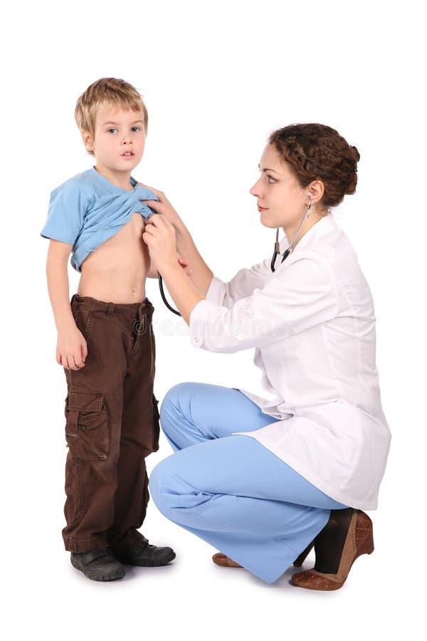 El doctor oye hacia fuera al niño al lado del estetoscopio imágenes de archivo libres de regalías