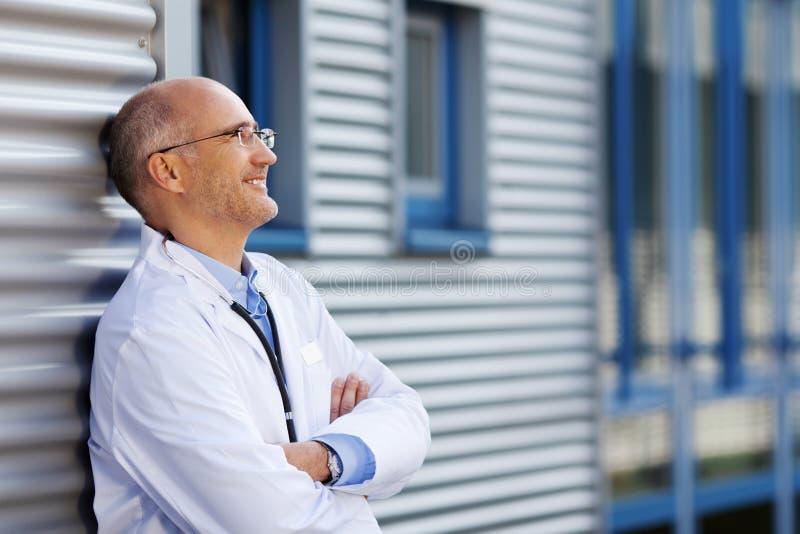 El doctor pensativo With Arms Crossed que sonríe mientras que se inclina en Wal foto de archivo libre de regalías