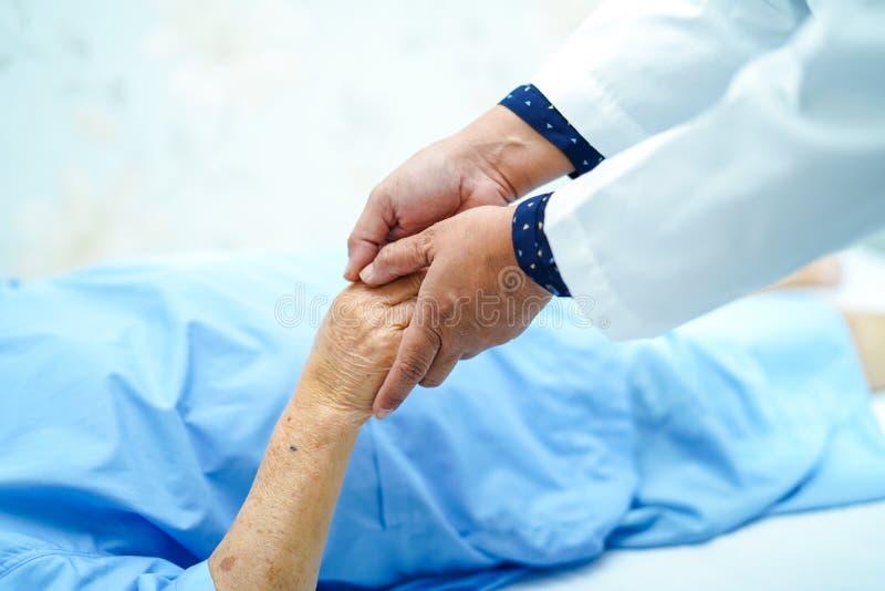 El doctor que celebra el tacto del paciente mayor de las manos o mayor asiático de la mujer de la señora mayor con el amor, cuida imagenes de archivo