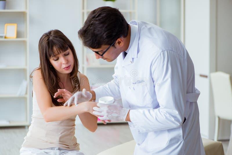El doctor que examina la piel del paciente femenino fotografía de archivo libre de regalías