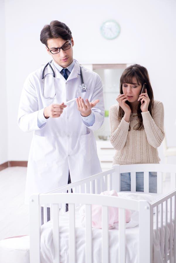 El doctor que explica a la madre joven fotografía de archivo