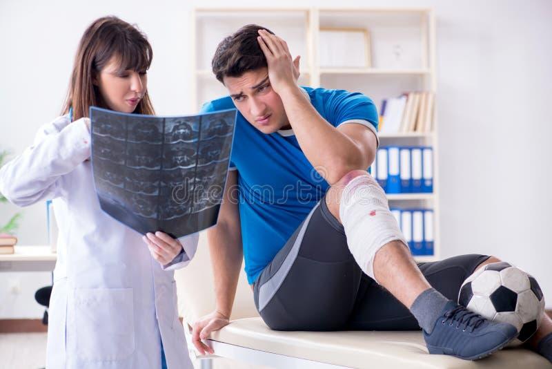 El doctor que visita del jugador de fútbol del fútbol después de lesión fotos de archivo