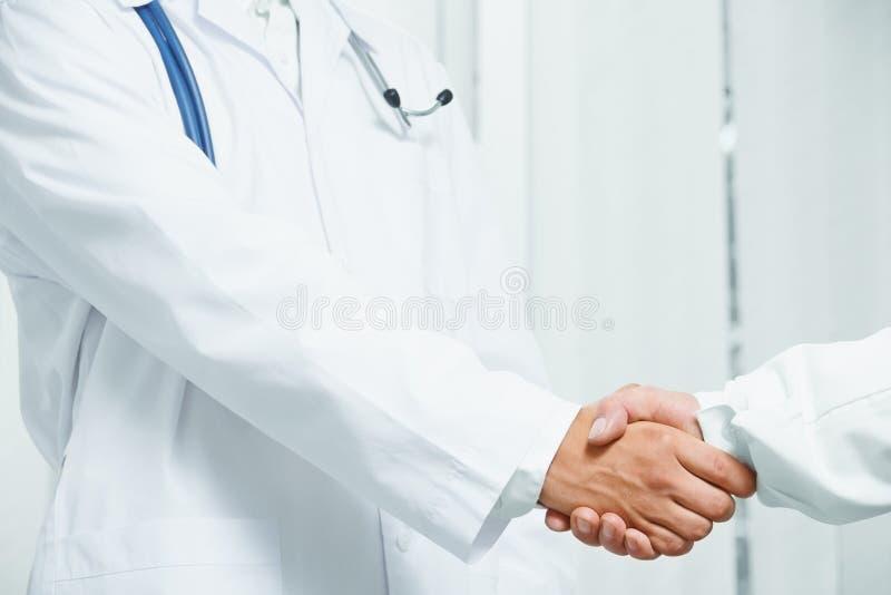 El doctor sacude la mano con otro doctor, trabajo en equipo fotos de archivo libres de regalías