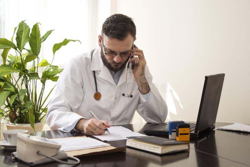 El doctor se sienta en su escritorio, tomando notas hablando en el teléfono fotografía de archivo