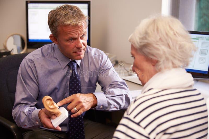 El doctor Showing Senior Female Of Human Ear modelo paciente fotos de archivo libres de regalías
