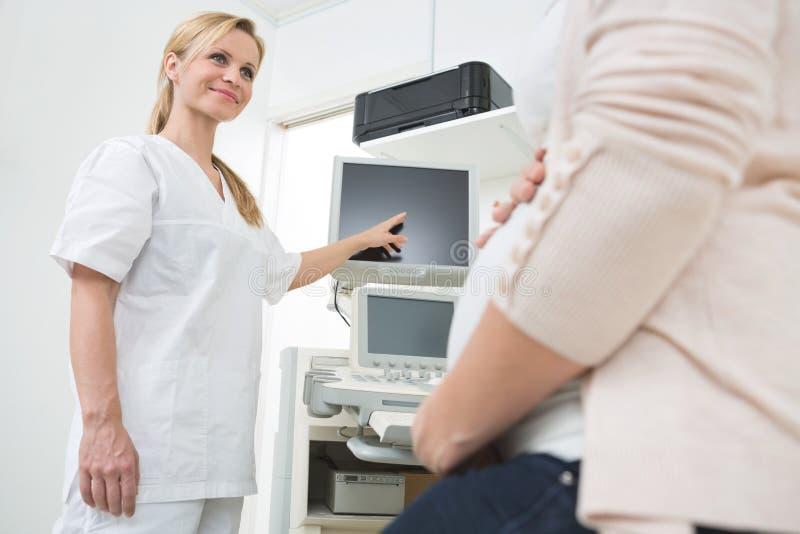 El doctor Showing Ultrasound Scan a la mujer embarazada fotos de archivo