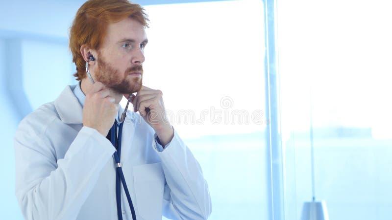 El doctor Sitting en clínica con el estetoscopio en oídos foto de archivo libre de regalías