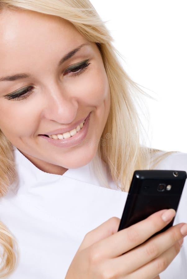 El doctor sonriente joven con el teléfono móvil imagen de archivo libre de regalías