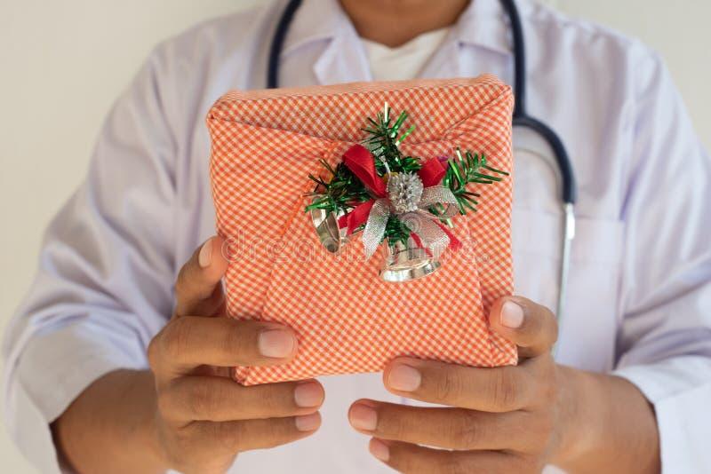 El doctor sostiene una caja de regalo, fotos de archivo