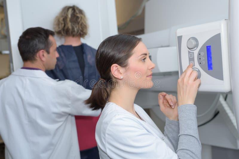 El doctor Standing Assisting Patient que experimenta la radiografía Tes del mamograma imagenes de archivo