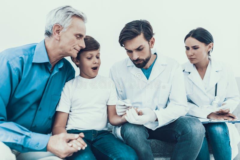 El doctor Taking Blood Sample del finger del ` s del muchacho foto de archivo