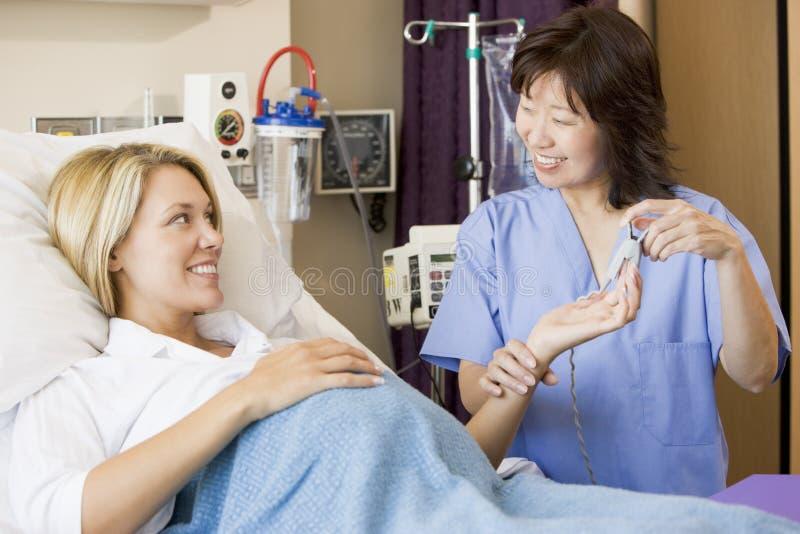 El doctor Taking Pregnant Womans Pulse imagen de archivo