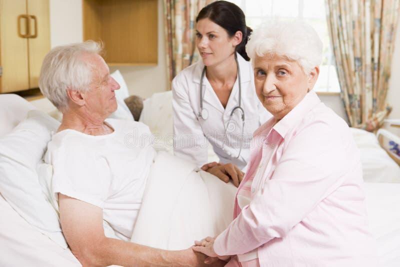 El doctor Talking To Senior Couple fotos de archivo