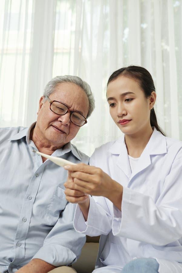 El doctor toma la temperatura del paciente fotografía de archivo