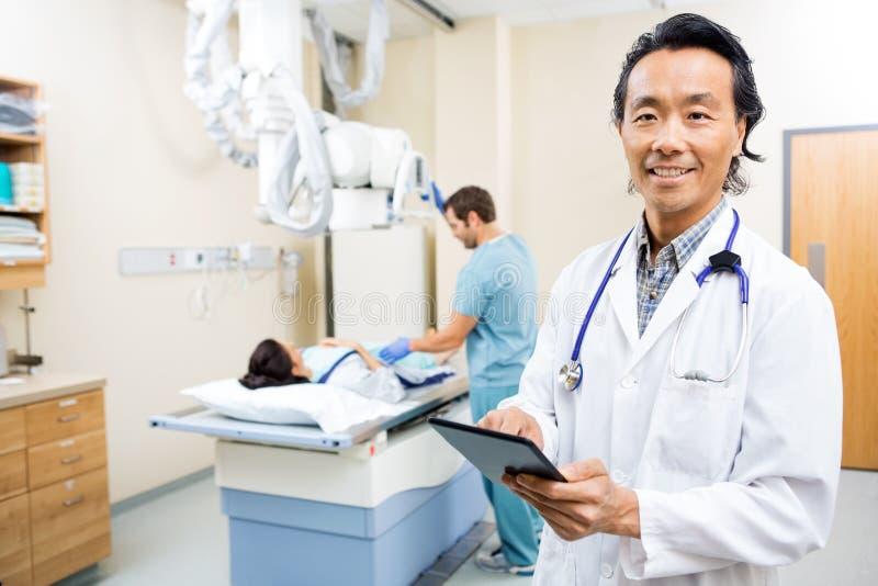 El doctor Using Digital Tablet en sitio de hospital imagenes de archivo