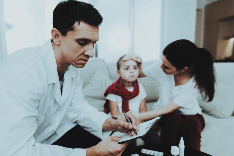 El doctor Visiting Little Girl en bufanda roja con frío Chica joven enferma Sofá blanco en sitio Doctor en uniforme concepto de l fotos de archivo libres de regalías