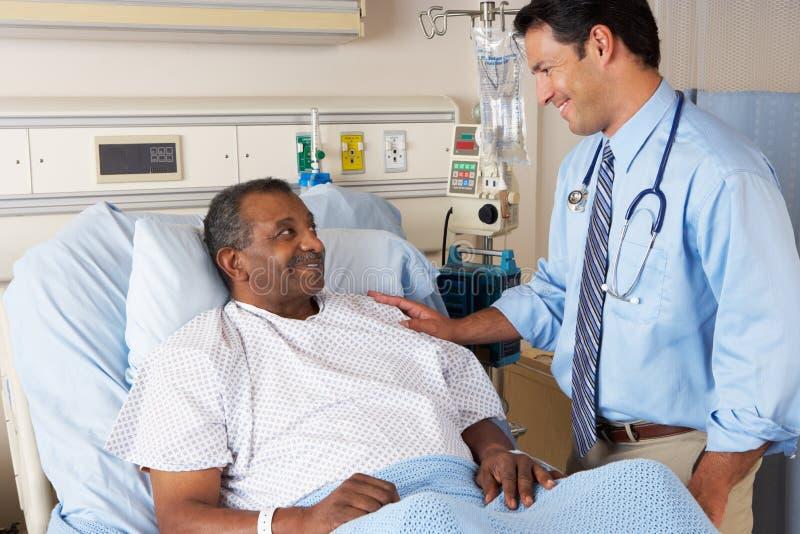 El doctor Visiting Senior Male Patient en sala fotografía de archivo