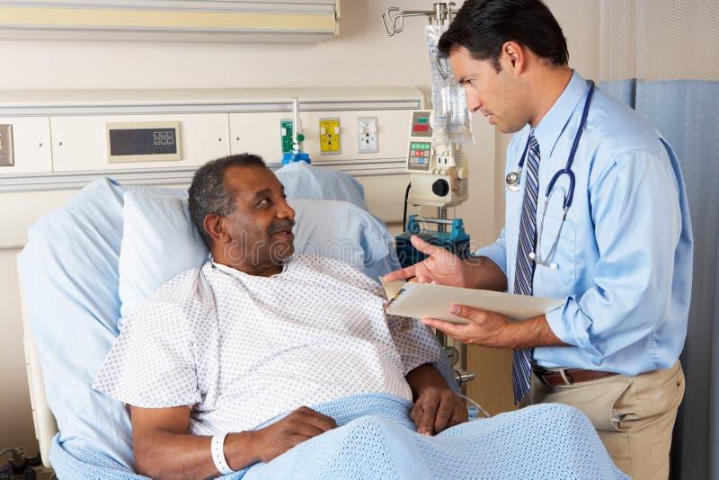El doctor Visiting Senior Male Patient en sala fotografía de archivo libre de regalías