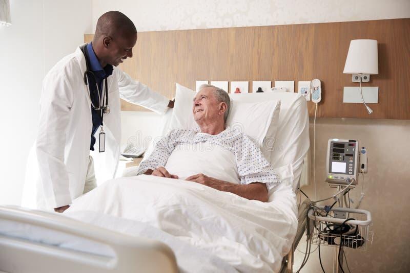 El doctor Visiting And Talking con el paciente masculino mayor en cama de hospital fotos de archivo