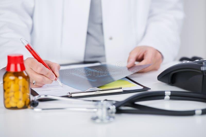 El doctor Writing Notes While que lleva a cabo la radiografía en el escritorio imagen de archivo libre de regalías