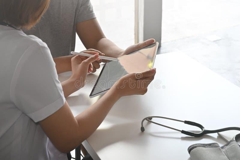 El doctor y el paciente están discutiendo con la tableta digital con consultan concepto fotos de archivo libres de regalías