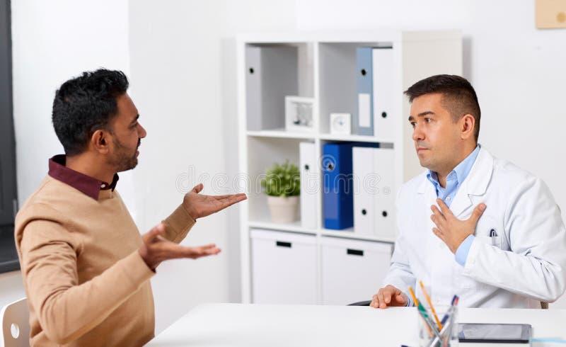 El doctor y el paciente masculino descontentado discuten en la clínica foto de archivo