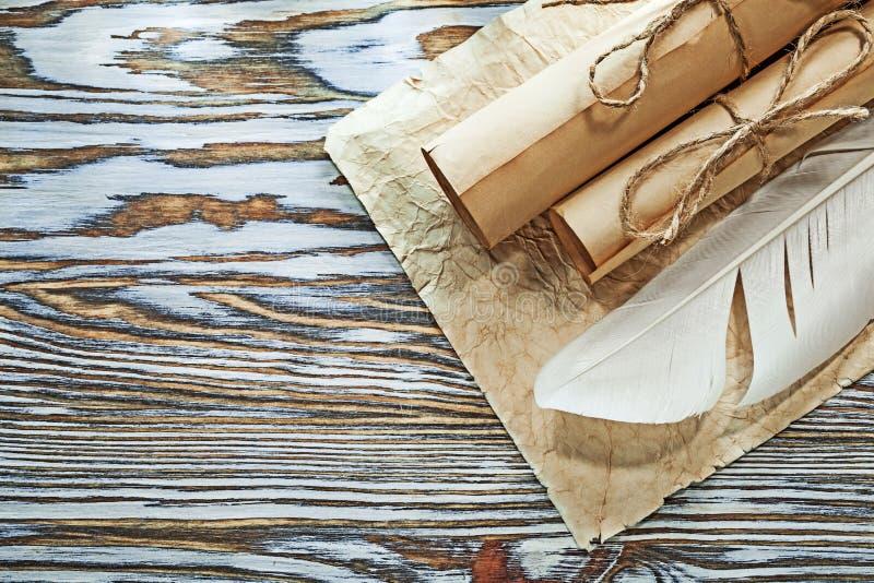 El documento arrugado los rollos de papel medievales plume en el tablero de madera fotografía de archivo