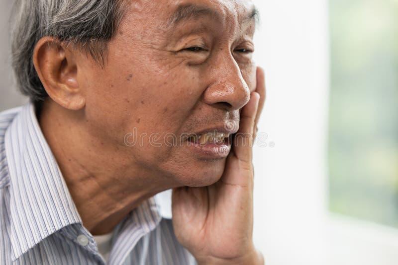 El dolor del dolor de muelas de la anciano del viejo hombre sufre de la carie dental de los dientes del problema decaída fotografía de archivo