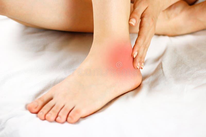 El dolor en su tobillo Mala pierna El foco del dolor se marca en r foto de archivo libre de regalías