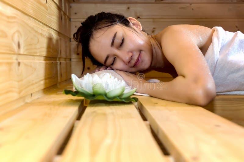 El dormir asiático joven hermoso de la muchacha se relaja, mintiendo en cabina de la sauna fotos de archivo libres de regalías