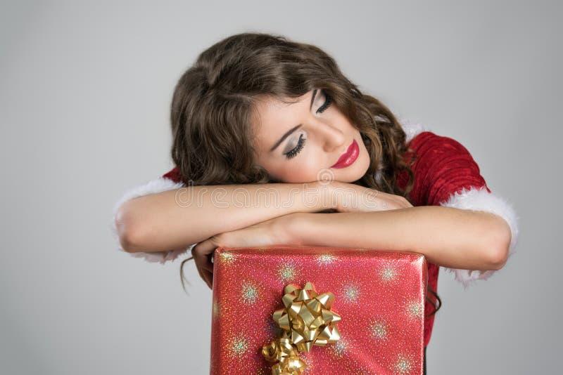 El dormir cansado de la muchacha del ayudante de Papá Noel cómodo en la caja roja grande con la cinta de oro fotografía de archivo