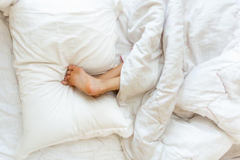 El dormir de la niña al revés y llevar a cabo pies en la almohada fotografía de archivo libre de regalías