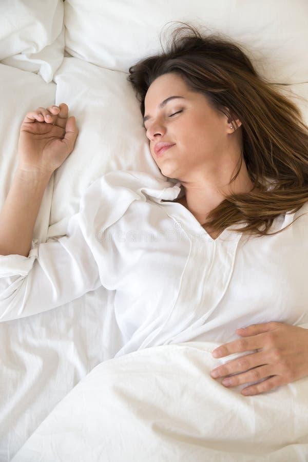 El dormir de relajación de la muchacha tranquila en las almohadas suaves en dormitorio imágenes de archivo libres de regalías