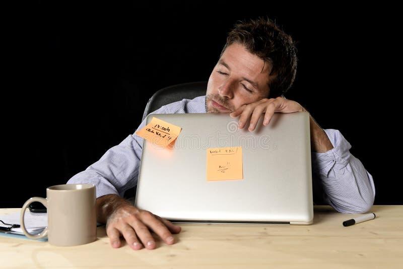 El dormir del hombre de negocios perdido cansado en el escritorio del ordenador de oficina en largases horas del trabajo fotografía de archivo
