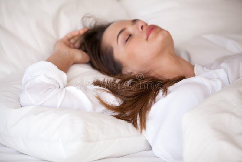 El dormir femenino joven tranquilo en la cama blanca acogedora que se relaja fotografía de archivo