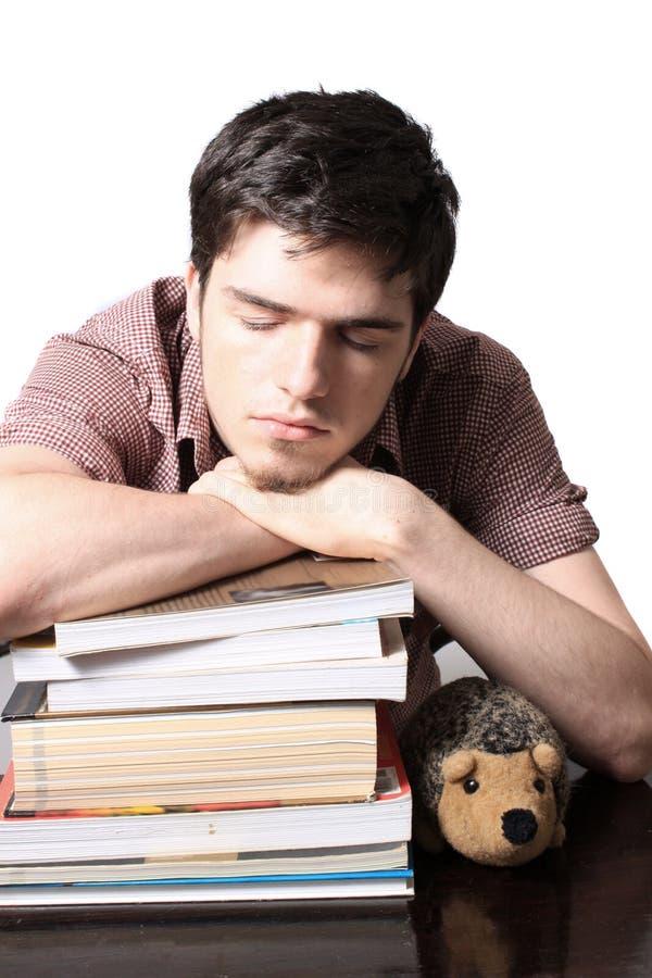 El dormir masculino adolescente en los libros foto de archivo