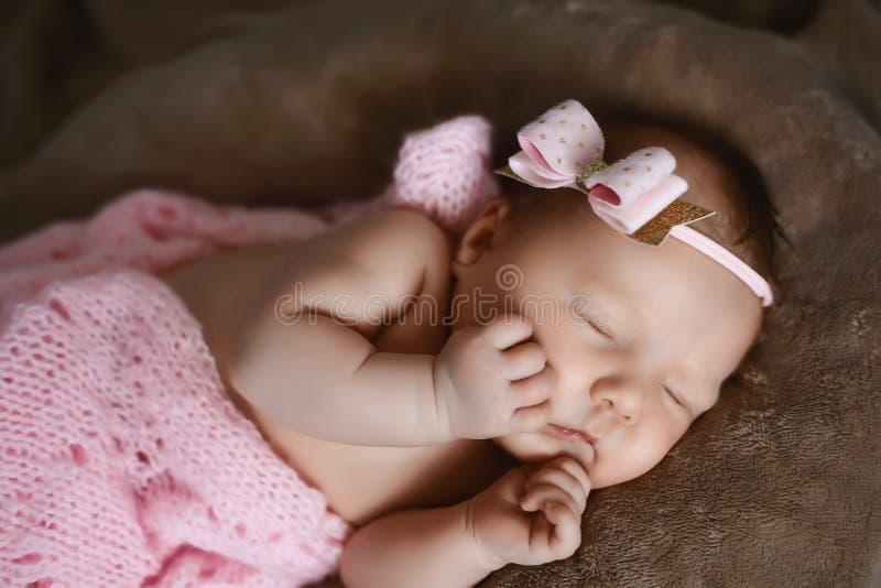 El dormir recién nacido del bebé lindo, cubierto con la bufanda rosada suave, doblada cuidadosamente debajo de una pluma con una  fotografía de archivo libre de regalías