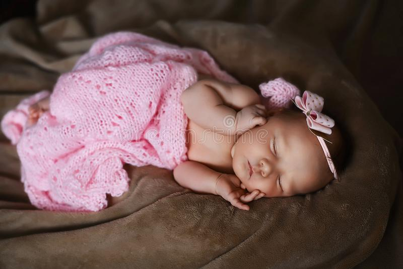 El dormir recién nacido del bebé lindo, cubierto con la bufanda rosada suave, doblada cuidadosamente debajo de una pluma con una  imágenes de archivo libres de regalías