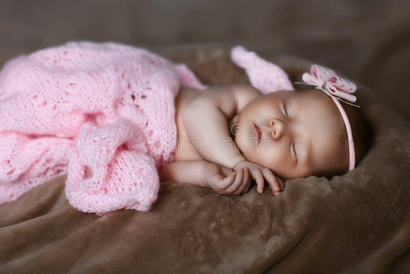 El dormir recién nacido del bebé lindo, cubierto con la bufanda rosada suave, doblada cuidadosamente debajo de una pluma con una  foto de archivo libre de regalías
