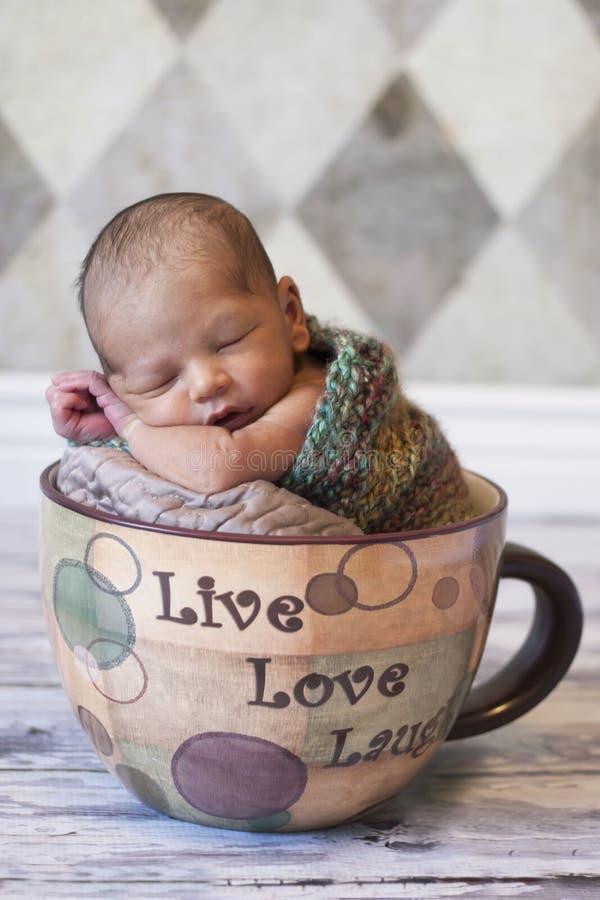 El dormir recién nacido en taza de café gigante imágenes de archivo libres de regalías