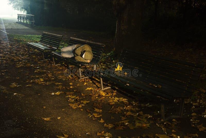 El dormir sin hogar en un banco foto de archivo