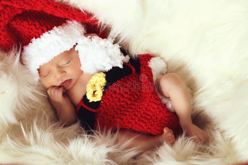 El dormir, viejo de tres semanas, recién nacido, bebé que lleva un sombrero hecho a ganchillo de Papá Noel fotos de archivo