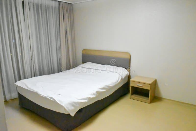 El dormitorio consiste en una cama, un estante, una ventana, una cortina imágenes de archivo libres de regalías