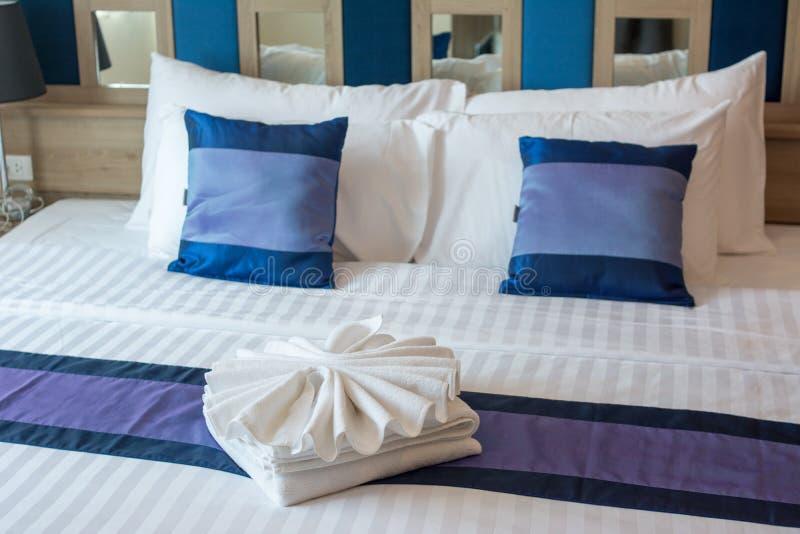 El dormitorio lujoso con las toallas diseña en la cama fotografía de archivo